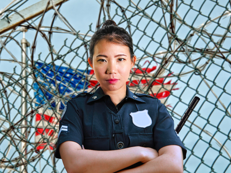 portrait of young serious and attractive Asian American guard woman standing at State penitentiary prison barbwire fence wearing police uniform in crime punishment and law concept
