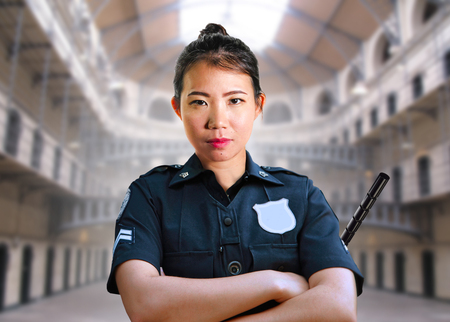 portrait of young serious and attractive Asian American guard woman standing at State penitentiary prison hall wearing police uniform in crime punishment and law enforcement concept