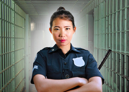 portrait of young serious and attractive Asian Korean guard woman standing on cell at State penitentiary wearing police uniform in crime prison punishment and law enforcement concept Banco de Imagens