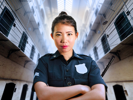 portrait of young serious and attractive Asian Chinese guard woman standing at State penitentiary prison hall wearing police uniform in crime punishment and law enforcement concept