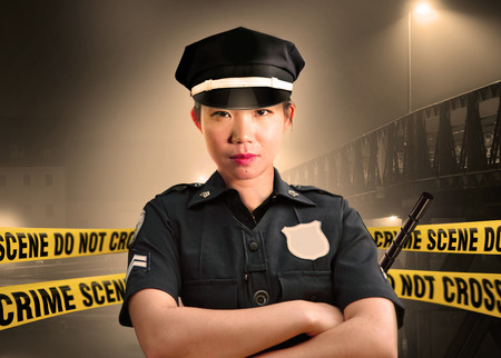 young Asian American police officer standing serious in custody of crime scene for preserving evidence at do not cross police line yellow tape in murder investigation and law enforcement concept Reklamní fotografie