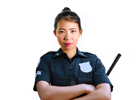 young attractive and defiant Asian Chinese police officer in uniform holding defense stick looking serious and inquisitive isolated on white background in law enforcement occupation