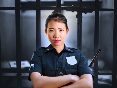 portrait of young serious and attractive Asian Chinese guard woman standing on cell at State penitentiary wearing police uniform in crime prison punishment and law enforcement concept