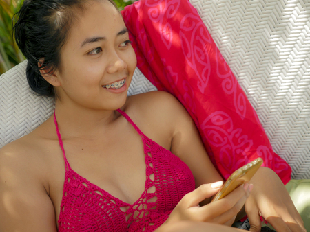 young happy and beautiful Asian Indonesian teenager girl in bikini smiling on pool bed with sarong using social media app on internet mobile phone relaxed at tropical resort enjoying Summer holidays