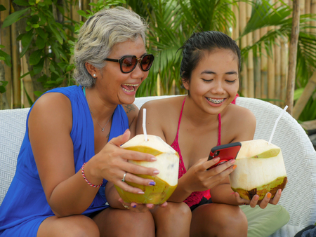 happy and beautiful Asian Indonesian teenager girl using mobile phone enjoying Summer holidays drinking coconut at tropical resort garden together with her mother, an attractive 40s woman
