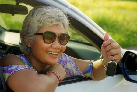 lifestyle portrait of attractive and happy middle aged Asian Indonesian woman 40s or 50s with grey hair and beautiful smile sitting in her new car holding key on window relaxed and cheerful