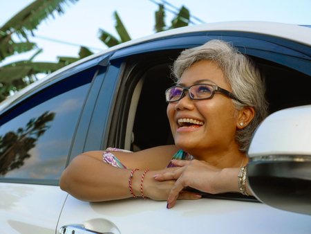 lifestyle portrait of attractive and happy middle aged Asian Indonesian woman 40s or 50s  with grey hair and beautiful smile sitting in her car enjoying nature looking through window relaxed and cheerful
