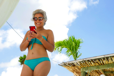 attractive and happy Asian Indonesian middle aged 40s or 50s woman in bikini at tropical resort swimming pool using social media app on mobile phone smiling relaxed enjoying holidays trip