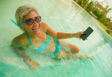 happy and attractive Asian Indonesian middle aged 40s or 50s woman taking selfie picture with mobile phone at tropical resort swimming pool enjoying holidays relaxed and cheerful