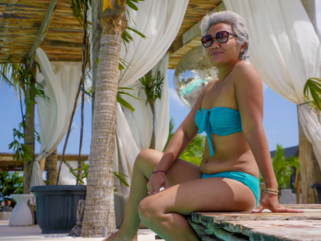 portrait of attractive and happy middle aged Asian Indonesian woman with grey hair enjoying holidays at tropical beach resort wearing blue bikini having fun relaxed at swimming pool Stock Photo