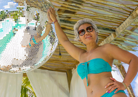 portrait of attractive and happy middle aged Asian Indonesian woman with grey hair enjoying holidays posing outdoors wearing blue bikini having fun in Summer holidays travel concept