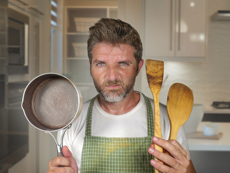 lifestyle portrait of young attractive unhappy and overwhelmed home cook man in apron holding spoon and pan feeling upset and lazy at house kitchen in domestic work and cooking duty 免版税图像