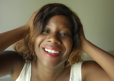portrait of young happy and beautiful black African American woman posing charming and playful smiling cheerful looking to the camera isolated on even background in female success concept
