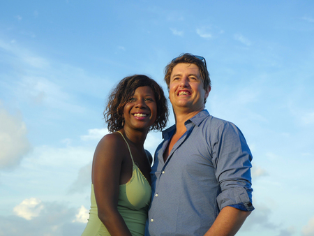 happy and beautiful mixed ethnicity couple with beautiful afro American woman and cheerful Caucasian man enjoying holidays honeymoon trip on beach cuddling sweet in multiracial love Banque d'images