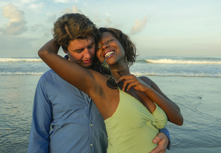 happy and romantic mixed race couple with attractive black African American woman and Caucasian man playing on beach having fun enjoying holidays in multiracial love relationship and diversity
