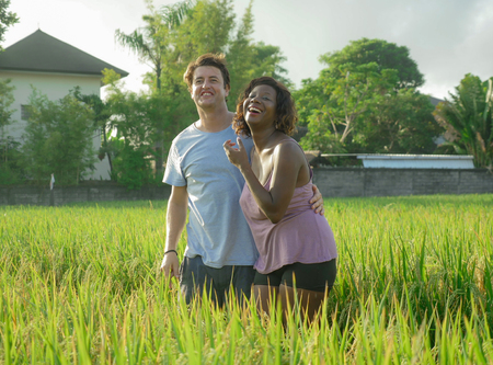 young happy and beautiful mixed ethnicity couple with black African American woman and attractive Caucasian man cuddling and having fun enjoying holidays at rice field in multiracial love Stock fotó