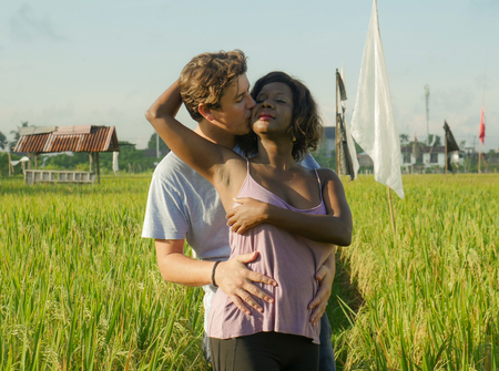 young happy and beautiful mixed ethnicity couple with black African American woman and attractive Caucasian man cuddling and having fun enjoying holidays at rice field in multiracial love