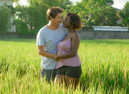 junges glückliches und schönes gemischtes ethnisches Paar mit schwarzer afroamerikanischer Frau und attraktiver kaukasischer Mann, die kuscheln und Spaß haben, Urlaub auf dem Reisfeld in multirassischer Liebe zu genießen