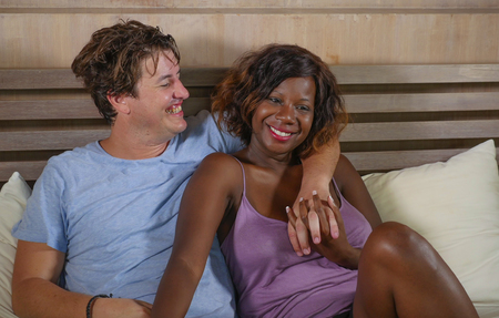 young happy and relaxed mixed ethnicity couple in love cuddling on bed with attractive black African American woman and handsome Caucasian boyfriend or husband in multi racial relationship
