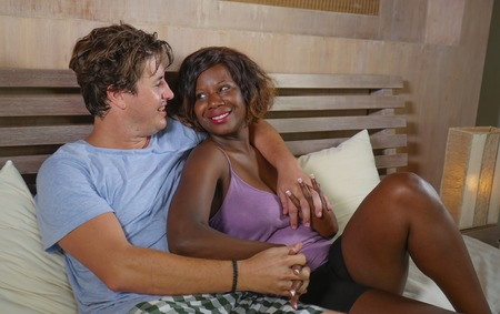 young happy and passionate mixed ethnicity couple in love kissing and smiling on bed with attractive black African American girlfriend or wife and handsome Caucasian man in multi racial relationship
