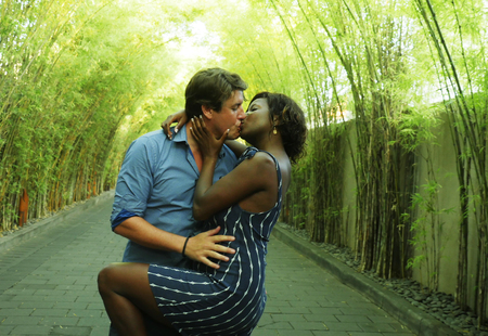 young attractive and happy mixed ethnicity couple kissing outdoors with attractive black African American girlfriend or wife and handsome Caucasian man in romantic trees background