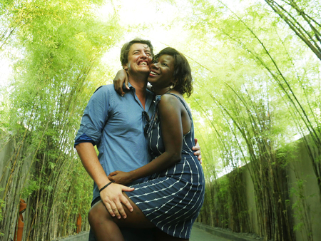 young attractive and happy mixed ethnicity couple cuddling outdoors with attractive black afro American girlfriend or wife and handsome Caucasian man  in romantic green trees background