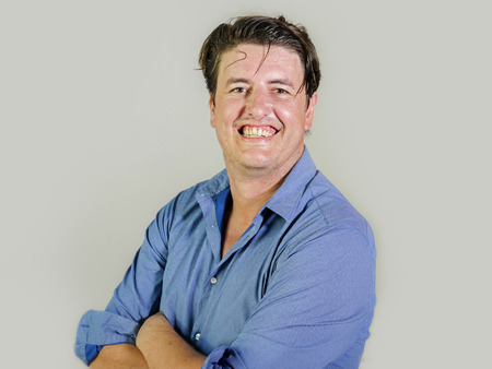 corporate portrait of young attractive and confident entrepreneur man in casual shirt smiling happy and positive looking at the camera in business success isolated on studio background