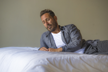 interior portrait of 30s to 40s happy and handsome man at home in casual shirt and jeans lying on bed relaxed at home thoughtful and pensive thinking about something in male lifestyle concept Stock Photo