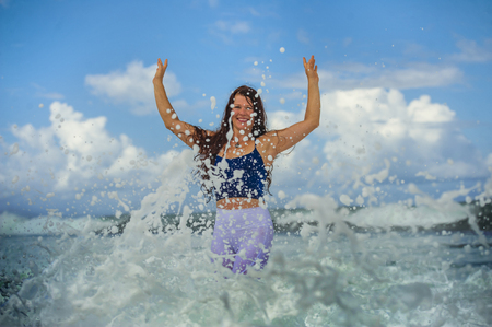 young happy and attractive red hair woman playing excited spreading arms feeling free and relaxed getting wet by sea waves splashing on her enjoying beach holidays trip and healthy lifestyle Stock Photo