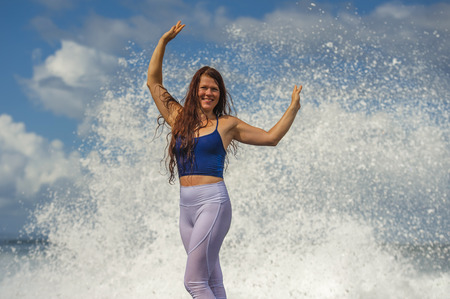 young happy and attractive red hair woman playing excited spreading arms feeling free and relaxed getting wet by sea waves splashing on her enjoying beach holidays trip and healthy lifestyle Foto de archivo