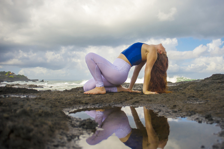 young happy attractive and beautiful red hair woman practicing yoga meditation and flexibility exercise at the beach on rocks in beautiful sea background in healthy lifestyle Stock Photo