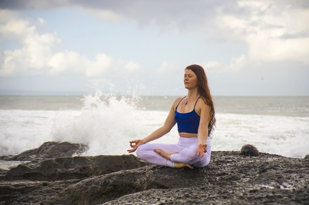 natural portrait of young attractive and happy red hair woman practicing meditation and relaxation yoga lotus exercise sitting at beach rock on the sea background in healthy lifestyle concept