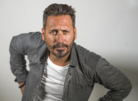 isolated portrait of young happy and handsome 40s man with blue eyes and beard  in casual shirt posing in cool attitude smiling cheerful and confident on studio background Stock Photo