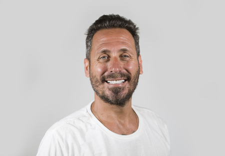 head and shoulders portrait of young happy and attractive man with blue eyes and beard looking cool smiling happy and confident wearing white t-shirt isolated on studio background
