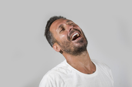 głowa i ramiona portret młodego szczęśliwego i atrakcyjnego mężczyzny z niebieskimi oczami i brodą, wyglądający fajnie, uśmiechnięty, szczęśliwy i pewny siebie, ubrany w białą koszulkę na białym tle na tle studia