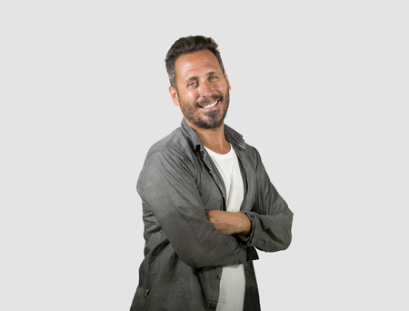 isolated portrait of young happy and handsome 40s man with blue eyes and beard in casual shirt posing in cool attitude smiling cheerful and confident on white studio background with folded arms