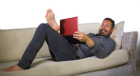 natural lifestyle portrait of young handsome and successful self employed man working at home using laptop computer lying relaxed at living couch networking cheerful in freelance business