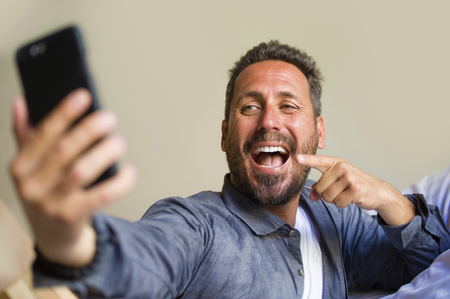lifestyle portrait of young attractive and happy 30s or 40s man taking selfie picture with mobile phone smiling playful gesturing at home bedroom lying on bed in casual clothes having social media fun
