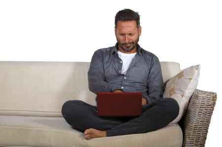natürliches Lifestyle-Porträt eines jungen, gutaussehenden und erfolgreichen Selbstständigen, der zu Hause mit Laptop-Computer arbeitet, der entspannt am lebenden Couch-Networking sitzt, fröhlich im freiberuflichen Geschäft Standard-Bild