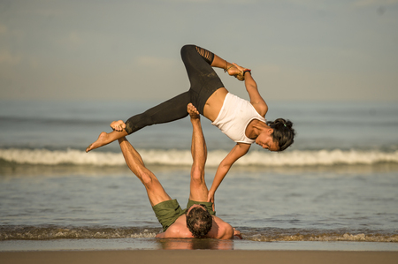 outdoors lifestyle portrait young attractive and concentrated couple of yoga acrobats practicing acroyoga balance and meditation exercise on beautiful beach in mind and body teamwork control Stock fotó