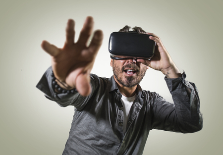 young happy and excited man wearing virtual reality VR goggles headset experimenting 3d illusion playing video game touching illusion environment surprised isolated on studio background 版權商用圖片