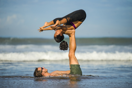 young attractive and concentrated couple of acrobats practicing acro yoga balance and meditation exercise on beautiful beach under a blue sky in mind and body control and healthy lifestyle