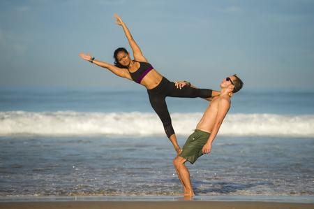 ritratto di stile di vita all'aperto giovane coppia attraente e concentrata di acrobati di yoga che praticano l'equilibrio di acroyoga e l'esercizio di meditazione sulla bellissima spiaggia nel controllo del lavoro di squadra della mente e del corpo Archivio Fotografico