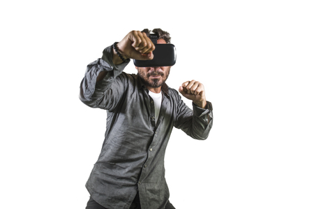 young happy and excited man wearing virtual reality VR goggles headset experimenting 3d illusion playing fight or boxing video game enjoying punching isolated on white background