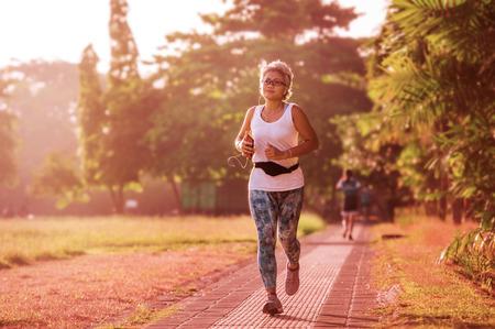 40er oder 50er Jahre glückliche und attraktive Frau mit grauem Haartraining im Stadtpark mit grünen Bäumen bei Sonnenaufgang, die Lauf- und Joggingtraining in Gesundheitsfitness und gesundem Lebensstil macht Standard-Bild