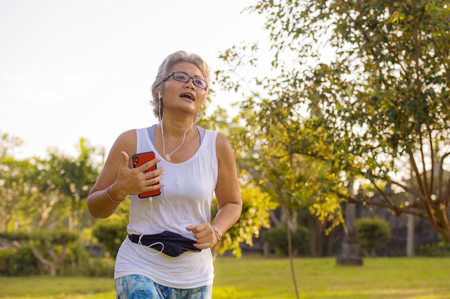 middle aged 40s or 50s happy and attractive woman with grey hair training at city park with green trees on sunrise doing running and jogging workout in health care fitness and healthy lifestyle