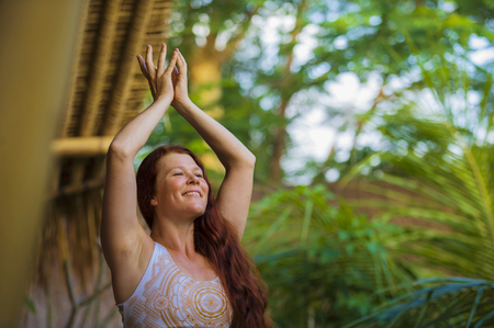 natural portrait of young happy and attractive woman with beautiful long red hair doing yoga meditation exercise at amazing tropical jungle background in healthy lifestyle and harmony