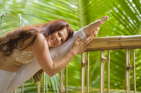 natural portrait of young happy and attractive woman with beautiful long red hair doing yoga flexibility exercise stretching leg at amazing tropical jungle background in healthy lifestyle in Bali