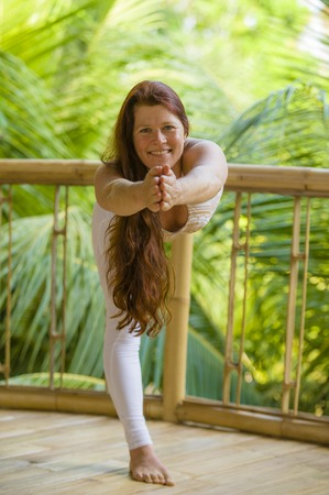 natural portrait of young happy and attractive woman with beautiful long red hair doing yoga meditation exercise at amazing tropical jungle background in healthy lifestyle and harmony in Bali