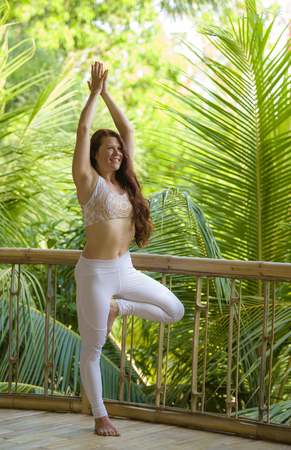 outdoors natural portrait of young beautiful and happy red hair woman doing yoga at tropical fitness studio practicing balance and concentration with jungle background in healthy lifestyle concept Imagens